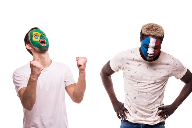 Szczęśliwy kibic brazylii świętuje zwycięstwo nad zdenerwowanym kibicem reprezentacji francji z pomalowaną twarzą na białym tle