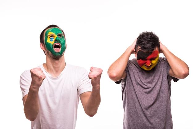 Szczęśliwy kibic brazylii świętuje zwycięstwo nad zdenerwowanym kibicem reprezentacji niemiec z pomalowaną twarzą na białym tle
