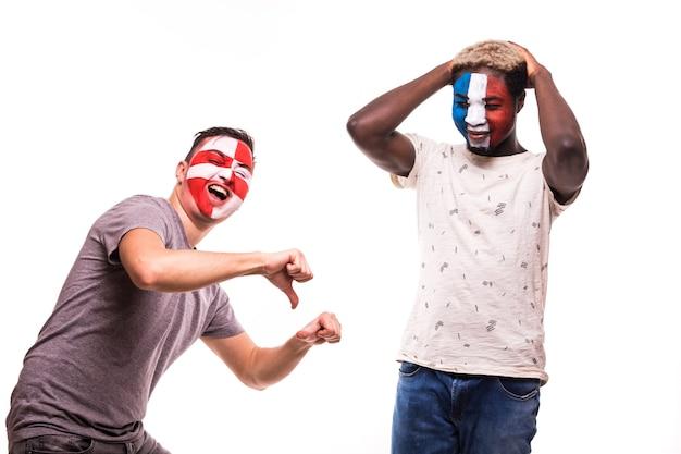 Szczęśliwy kibic chorwacji świętuje zwycięstwo nad zdenerwowanym kibicem francji z pomalowaną twarzą na białym tle
