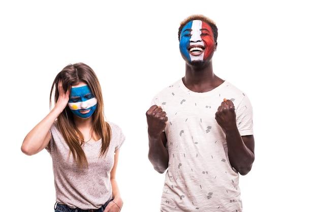 Szczęśliwy kibic francji świętuje zwycięstwo nad zdenerwowanym kibicem argentyny z pomalowaną twarzą