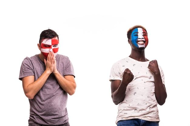 Szczęśliwy kibic francji świętuje zwycięstwo nad zdenerwowanym kibicem chorwacji z pomalowaną twarzą na białym tle