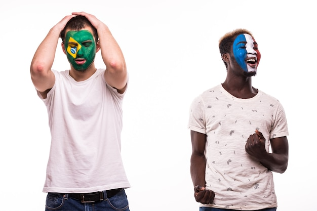 Szczęśliwy kibic francji świętuje zwycięstwo nad zdenerwowanym kibicem reprezentacji brazylii z pomalowaną twarzą na białym tle