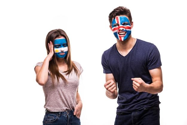 Szczęśliwy kibic islandii świętuje zwycięstwo nad zdenerwowanym kibicem argentyny z pomalowaną twarzą na białym tle