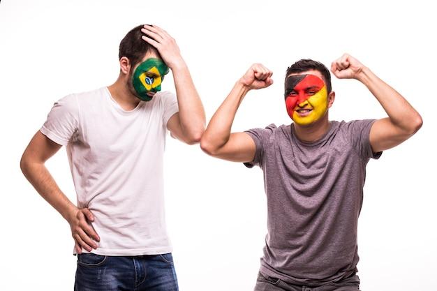 Szczęśliwy kibic niemiec świętuje zwycięstwo nad zdenerwowanym kibicem reprezentacji brazylii z pomalowaną twarzą na białym tle