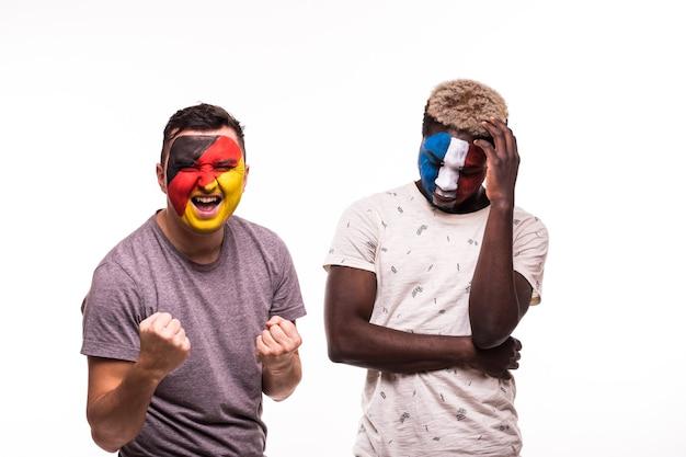 Szczęśliwy kibic niemiec świętuje zwycięstwo nad zdenerwowanym kibicem reprezentacji francji z pomalowaną twarzą na białym tle