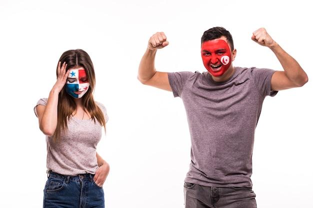 Szczęśliwy kibic tunezji świętuje zwycięstwo nad zdenerwowanym kibicem panamy z pomalowaną twarzą na białym tle