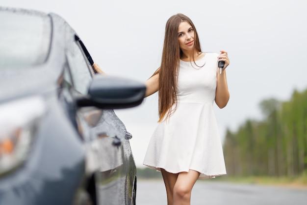 Szczęśliwy kierowca kobieta pokazuje kluczyki do samochodu i opierając się na drzwiach samochodu