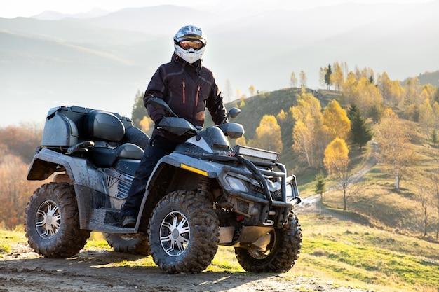Szczęśliwy kierowca mężczyzna w kasku ochronnym, ciesząc się ekstremalną jazdą na quadzie atv w jesiennych górach o zachodzie słońca.