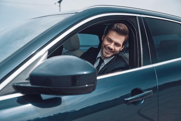 Szczęśliwy kierowca. przystojny młody mężczyzna w pełnym garniturze, patrząc prosto podczas jazdy samochodem