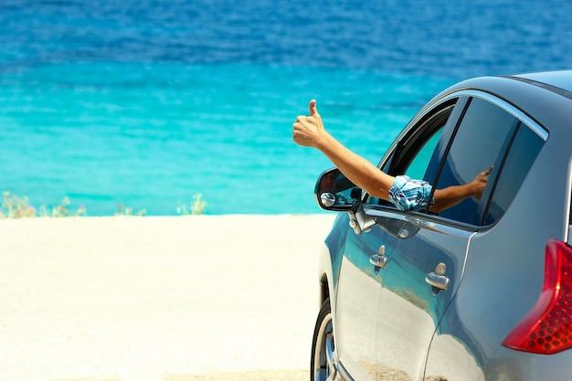 Szczęśliwy kierowca w samochodzie na morzu w lecie koncepcja wolności i szczęścia