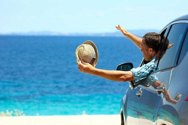 Szczęśliwy kierowca z kapeluszem w samochodzie na morzu w lecie koncepcja wolności i szczęścia