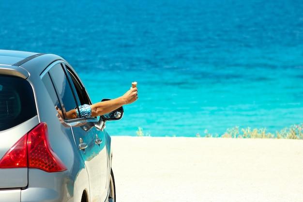Szczęśliwy kierowca z lodami w samochodzie na morzu w lecie koncepcja wolności i szczęścia