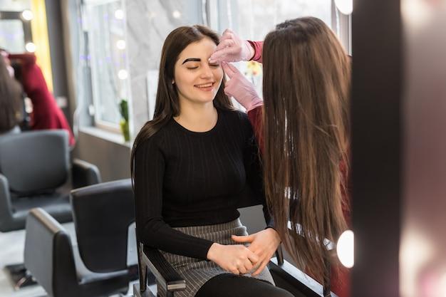 Szczęśliwy klient czeka na końcowy efekt makijażu wieczorowego