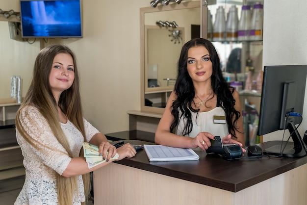 Szczęśliwy klient dając dolary recepcjonistce w salonie
