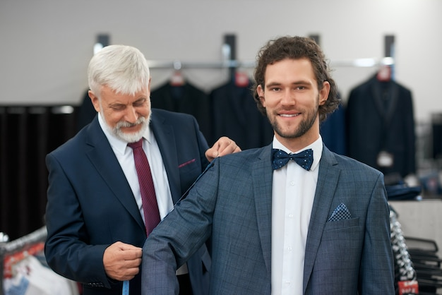 Szczęśliwy klient dopasowujący modne garnitury.