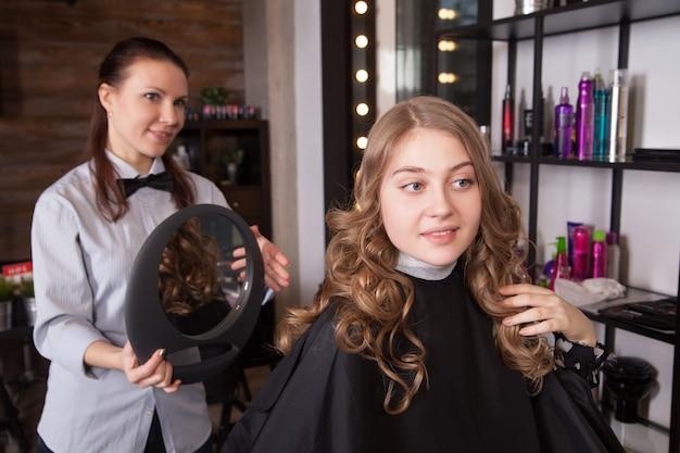 Szczęśliwy klient patrząc w lustro w salonie. stylistka stojąca za krzesłem