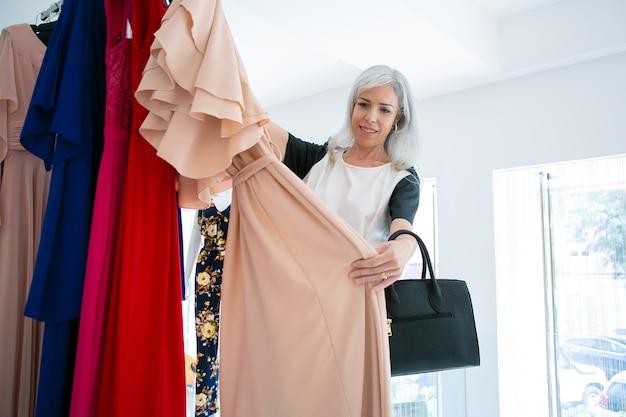 Szczęśliwy klient płci żeńskiej gospodarstwa wieszak z sukienką, patrząc na szmatkę i uśmiechnięty. sredni strzał. koncepcja sklepu mody lub sprzedaży detalicznej
