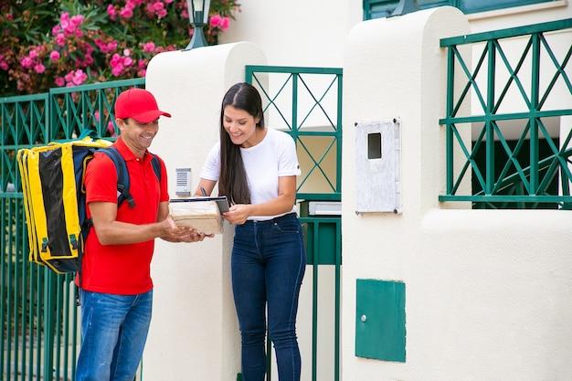 Szczęśliwy klient płci żeńskiej podpisywanie w arkuszu dostawy za pomocą pióra. uśmiechnięty kurier z żółtym plecakiem trzymającym paczkę i schowek, stojący i ubrany w czerwony mundur. usługa dostawy i koncepcja poczty