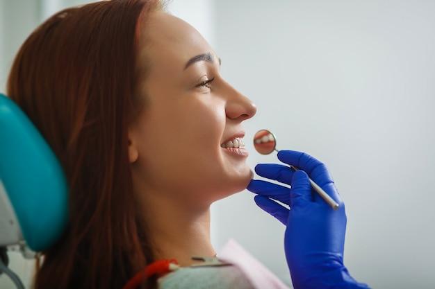 Szczęśliwy klient u dentysty uśmiecha się. wybielanie zębów.