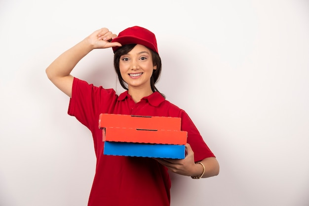 Szczęśliwy kobieta dostawa pizzy pracownik stojący z trzema kartonami pizzy.