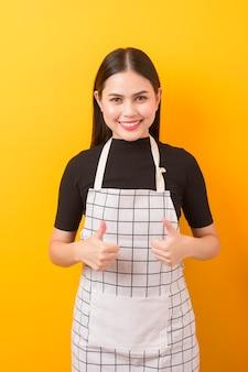 Szczęśliwy kobieta kucharza portret na kolorze żółtym