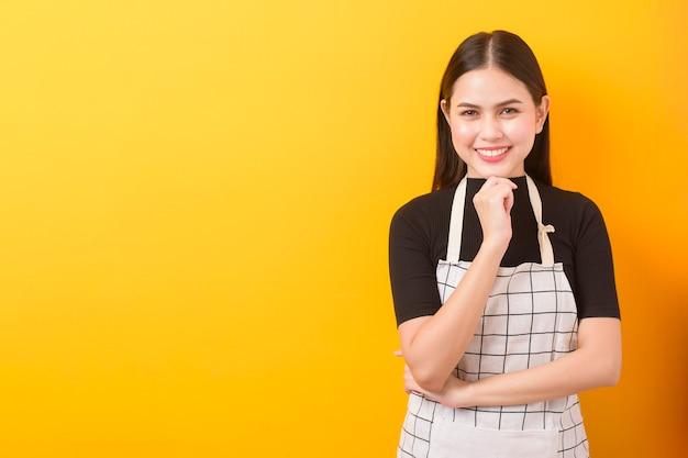 Szczęśliwy kobieta kucharza portret na żółtym tle