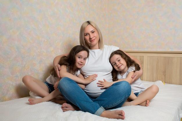Szczęśliwy kobieta w ciąży z jej córkami siedzi na łóżku w domu. szczęśliwa rodzina w izolacji. dzieci kochają swoją matkę