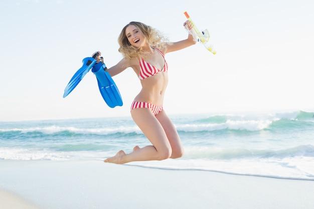 Szczęśliwy kobiety doskakiwanie podczas gdy trzymający flippers, snorkel i nurkowych gogle