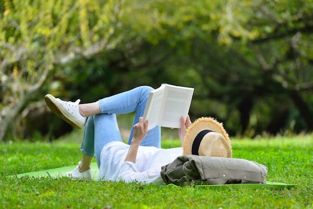 Szczęśliwy kobiety lying on the beach na zielonej trawie czyta książkę w parku