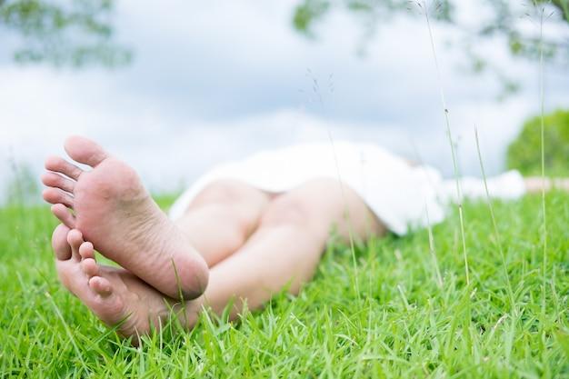 Szczęśliwy kobiety lying on the beach na zielonej trawy łące