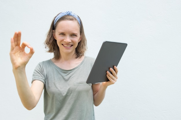 Szczęśliwy kobiety mienia gadżet, używać pastylka komputer osobistego
