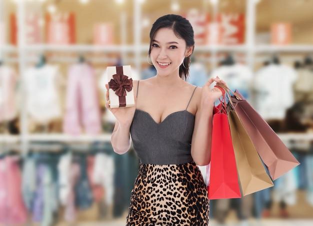 Szczęśliwy kobiety mienia prezenta pudełko i torba na zakupy przy centrum handlowym