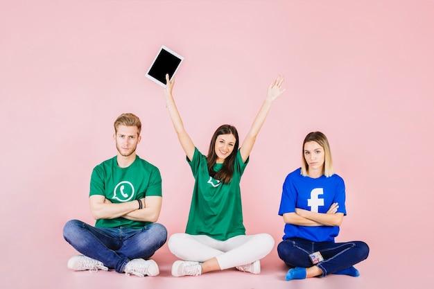 Szczęśliwy kobiety obsiadanie między jej dwa smutnymi przyjaciółmi z rękami podnosić