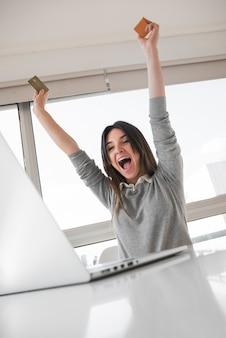 Szczęśliwy kobiety obsiadanie przy stołem z laptopem