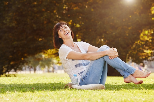 Szczęśliwy kobiety obsiadanie w trawie z ciekami w powietrzu