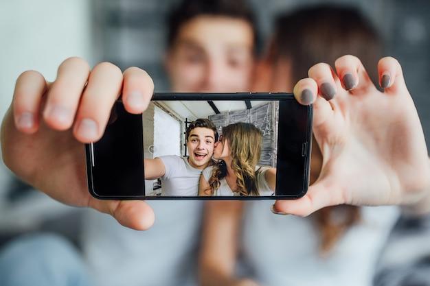 Szczęśliwy kochanek korzystający z inteligentnego telefonu technologicznego do selfie na łóżku w sypialni w domu