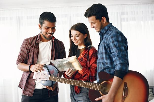 Szczęśliwy krąg przyjaciół planujących podróż. globe trotters sprawdzające mapę będąc w domu. pochodzenie etniczne europejskie i indyjskie. mężczyźni posiadający gitarę i kulę ziemską.