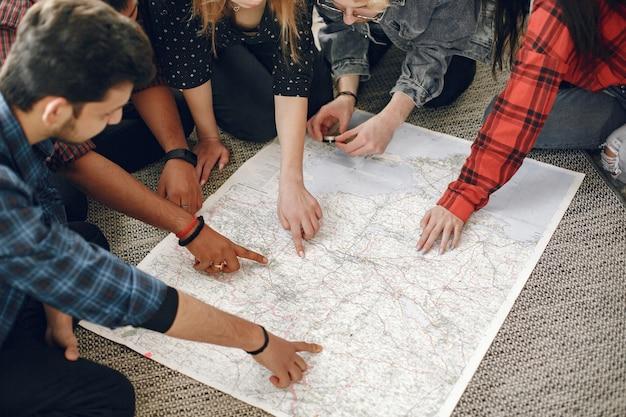 Szczęśliwy krąg przyjaciół planujących podróż. globe trotters sprawdzające mapę będąc w domu. pochodzenie etniczne europejskie i indyjskie.