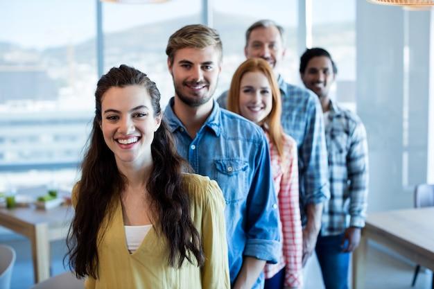 Szczęśliwy kreatywny biznes zespół stojący w linii w biurze