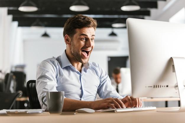 Szczęśliwy krzyczący biznesmen przy użyciu komputera i raduje się, siedząc przy stole w biurze