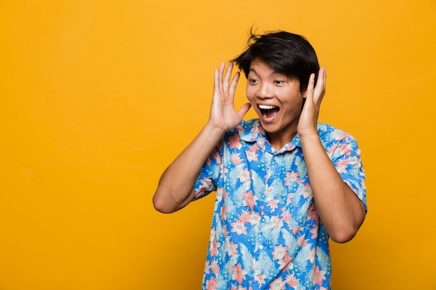 Szczęśliwy krzyczący emocjonalny młody człowiek azjatycki pozowanie na białym tle nad żółtą przestrzenią.