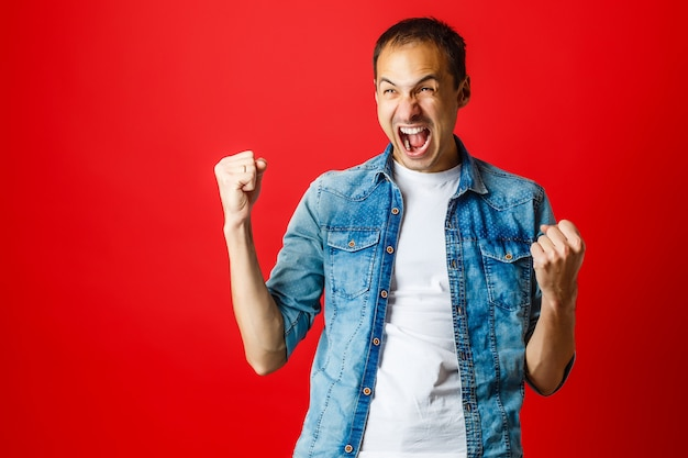 Szczęśliwy krzyczący mężczyzna na czerwonym tle