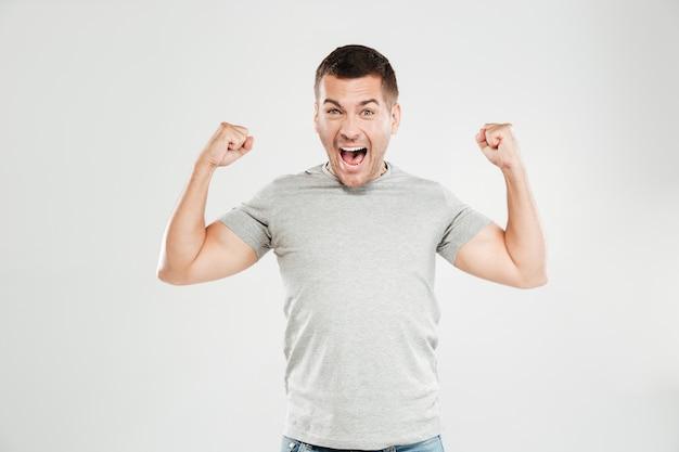 Szczęśliwy krzyczący mężczyzna pokazuje bicepsy.