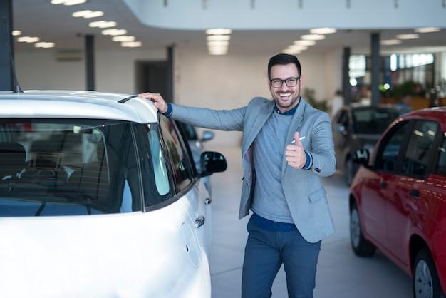 Szczęśliwy kupujący samochód lub sprzedawca samochodów stojący przy nowym pojeździe w salonie dealerskim trzymając kciuki do góry.