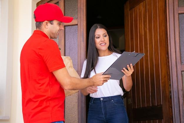 Szczęśliwy kurier pokazujący klientowi arkusz zamówienia i trzymający schowek. profesjonalny dostawca niosący papierową torbę. kobieta odbiera zamówienie w domu. dostawa żywności i koncepcja zakupów online
