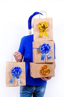 Szczęśliwy kurier w niebieskim mundurze i czapce mikołaja posiada wiele pudełek i paczek z prezentami