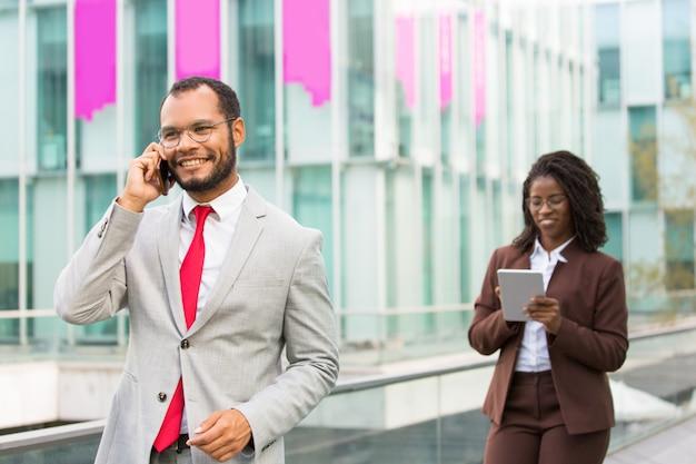Szczęśliwy łaciński biznesmen opowiada na telefonie komórkowym