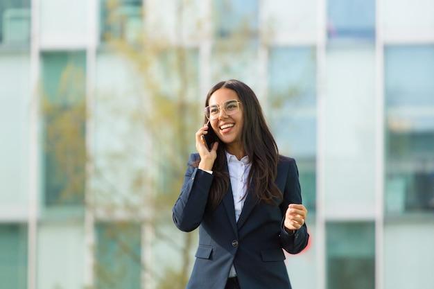 Szczęśliwy łaciński bizneswoman opowiada na telefonie komórkowym