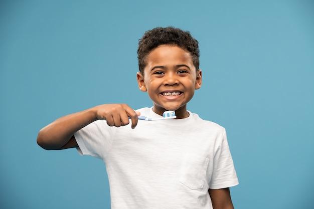 Szczęśliwy ładny afrykański lub mieszanej rasy mały chłopiec ze szczoteczką do zębów będzie myć zęby na niebiesko