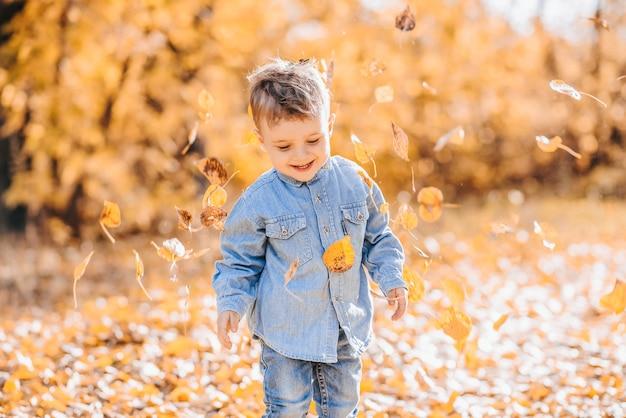 Szczęśliwy ładny chłopiec bawi się jesiennymi liśćmi w parku